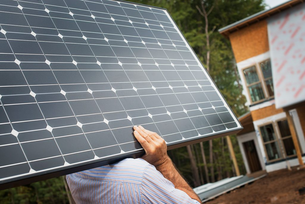 man carrying solar panel to install in Busselton home