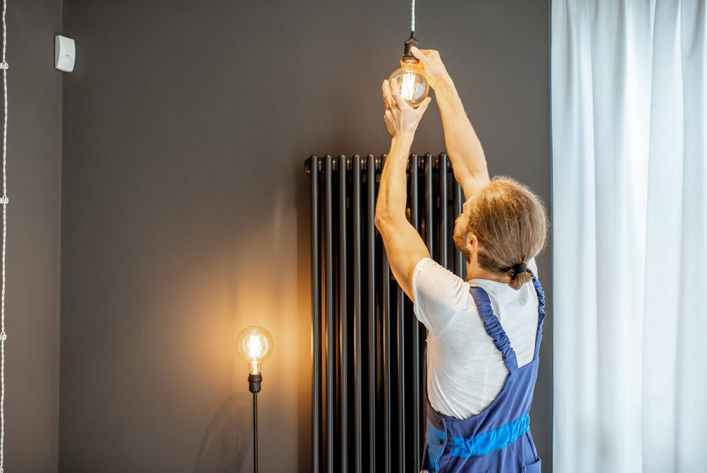 handyman replacing lightbulb at home